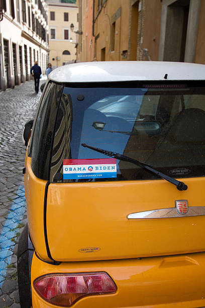 obama-biden bumper sticker on little yellow car, cobbled street, rome - joe biden stok fotoğraflar ve resimler
