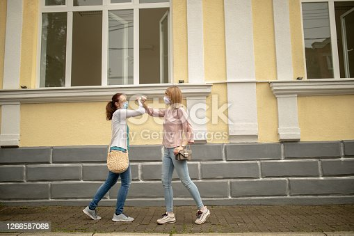 Two women greeting each other by bumping elbows gesture on the street keeping social distance, preventing spreading Corona virus.