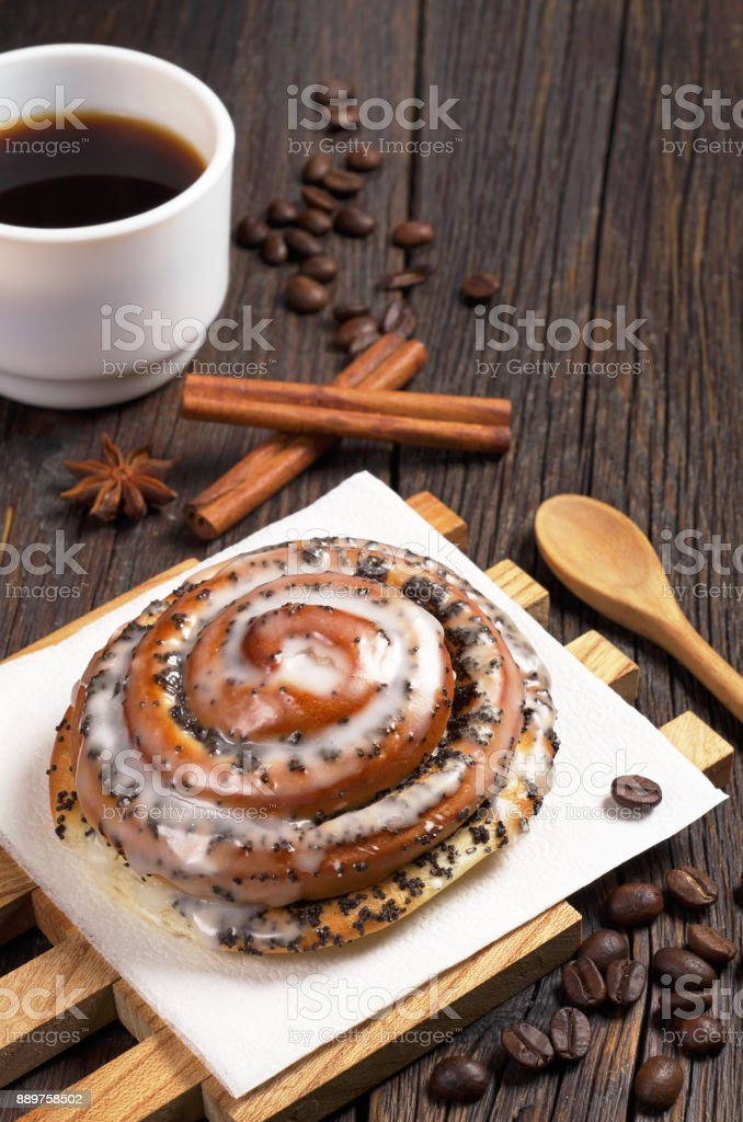 Bun with poppy seeds and sugar icing and cup of black coffee on old...