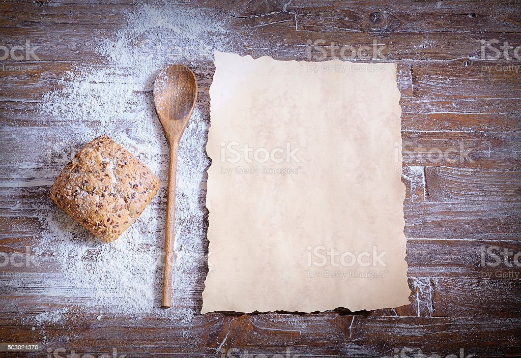 Bun with sesame, scattered flour, spoon and baking paper stock photo