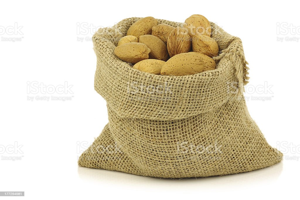 bunch of almond nuts in a burlap bag royalty-free stock photo