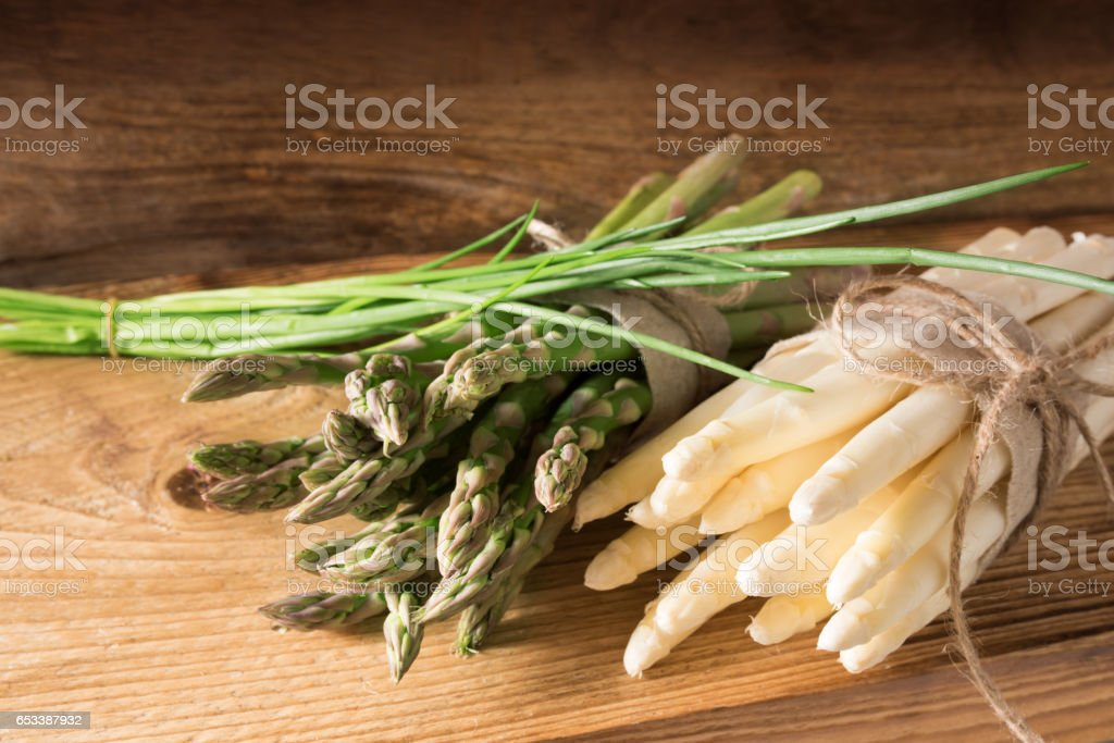 Bunch of asparagus with chives on wood stock photo
