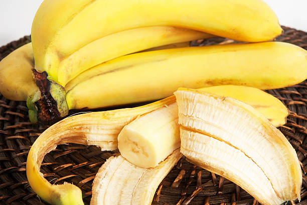 Bunch of bananas and one peeled banana. One peeled banana and bunch of bananas on wicker plate. banana peel stock pictures, royalty-free photos & images