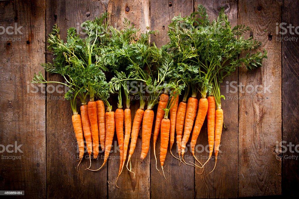 A bunch of fresh organic carrots, shot overhead on a worn rustic...