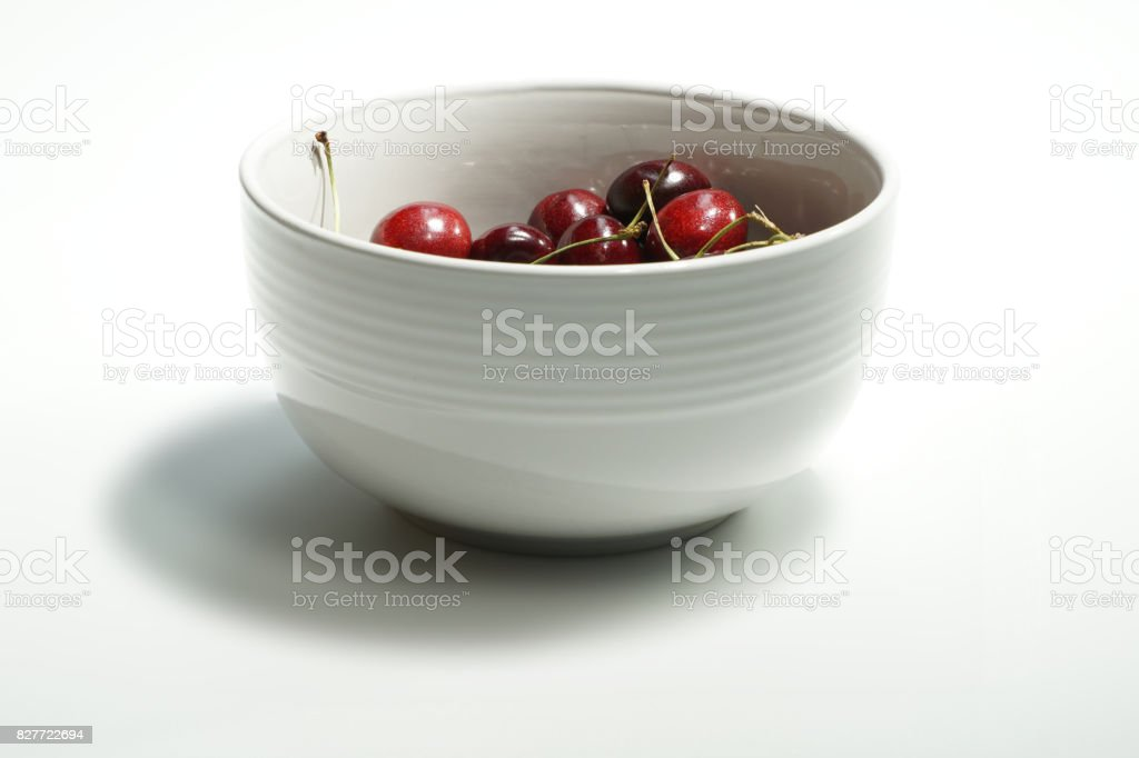 Bunch of cherries in a white bowl stock photo