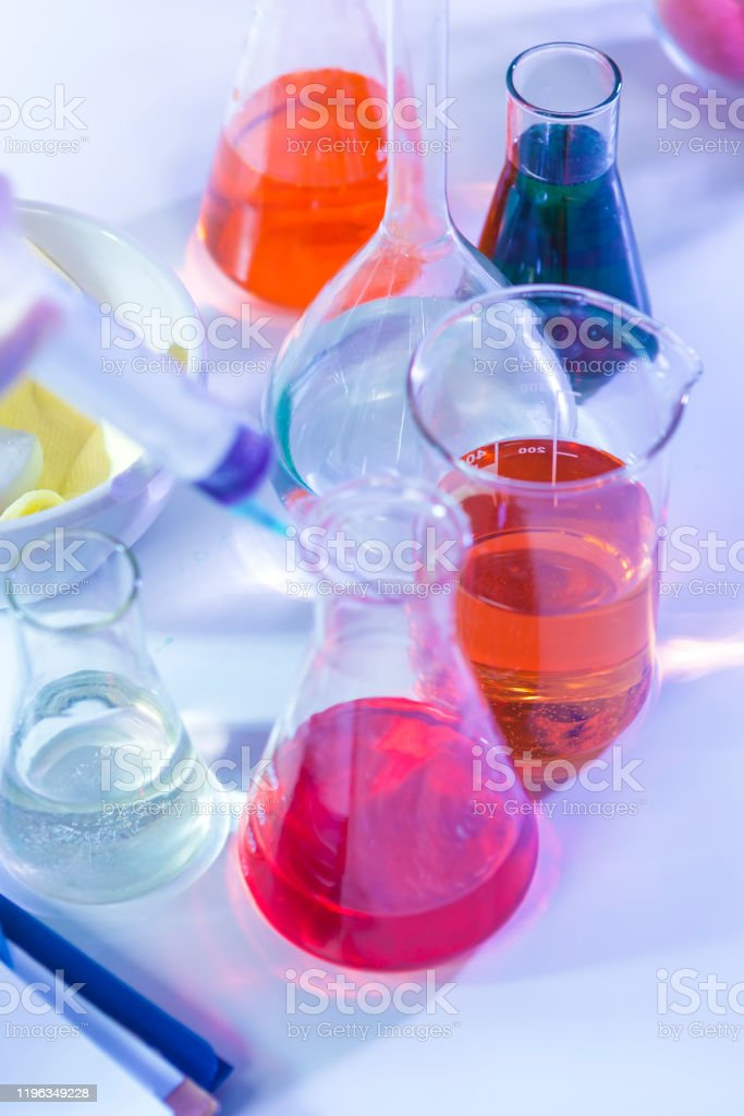 Bunch of Colorful Liquid Chemicals in Flasks Placed in Lab.Vertical Image Composition Bunch of Colorful Liquid Chemicals in Flasks Placed in Lab.Vertical Image Composition Beaker Stock Photo
