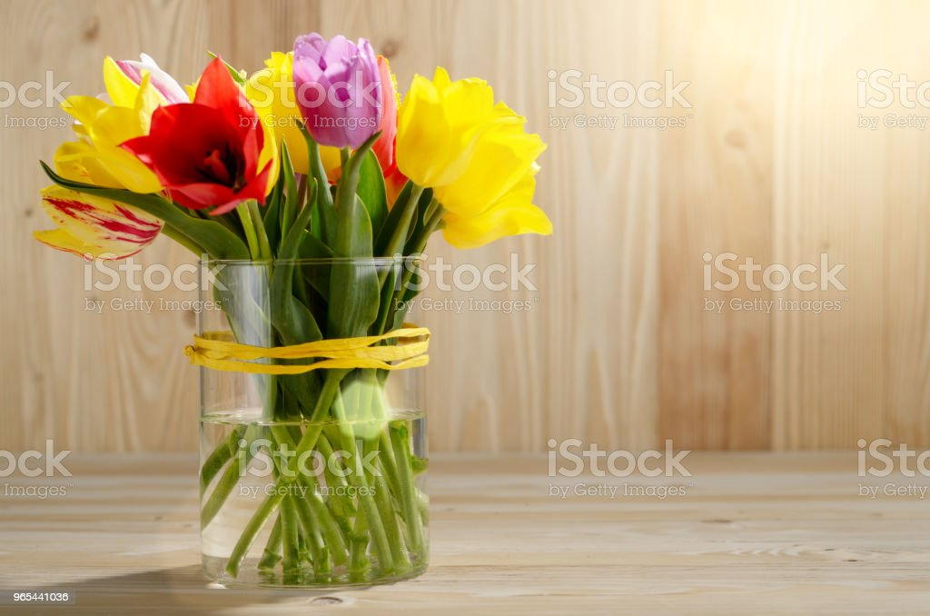 Bunch of Colorful tulip flowers in glass vase on wooden table background with space for text royalty-free stock photo