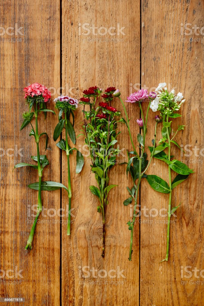 bunch of colorful wild flowers on wooden table stock photo