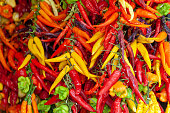 A bunch of different colorful chilies nicely arranged on a market to be sold.