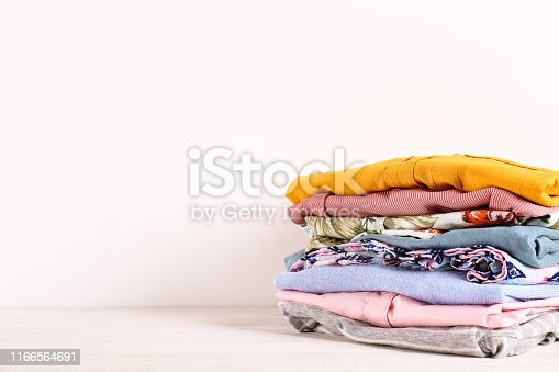 istock Bunch of different colorful clothing items folded in stack. 1166564691