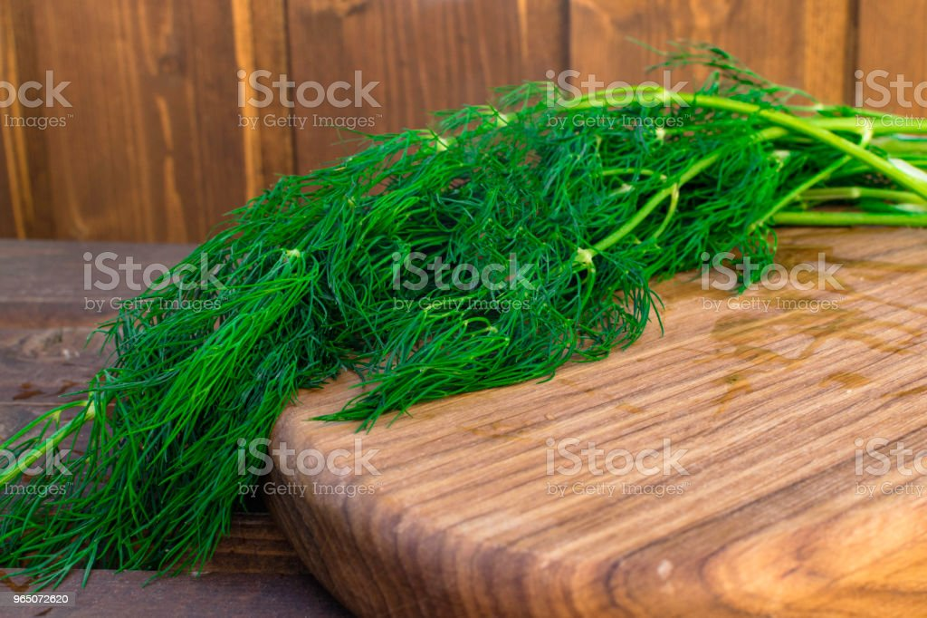 Bunch of dill isolated on a wooden background with space for text. Selective focus. Food for vegetarians royalty-free stock photo