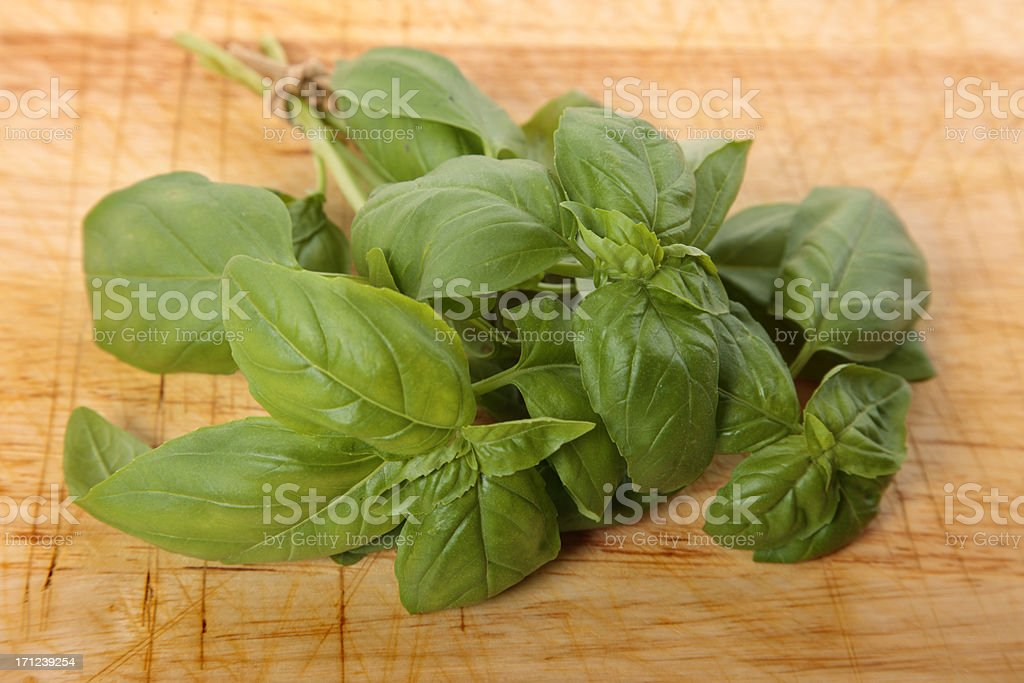 Bunch of fresh basil on a wooden chopping board.Alternative image in...
