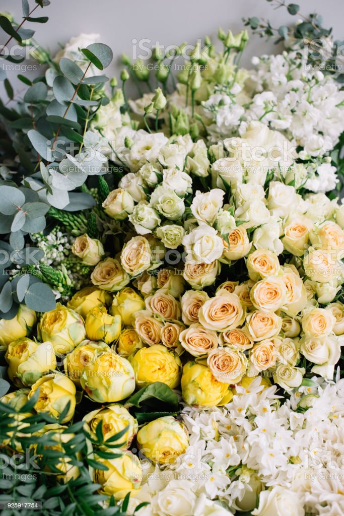 Bunch of fresh blossoming flowers at the florist shop: roses, yellow...