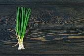 Bunch of fresh green onions  in bundle on breadboard table