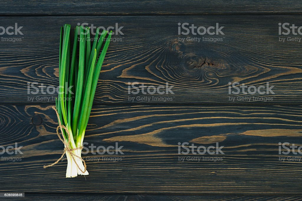 Bunch of fresh green onions  in bundle on breadboard table stock photo