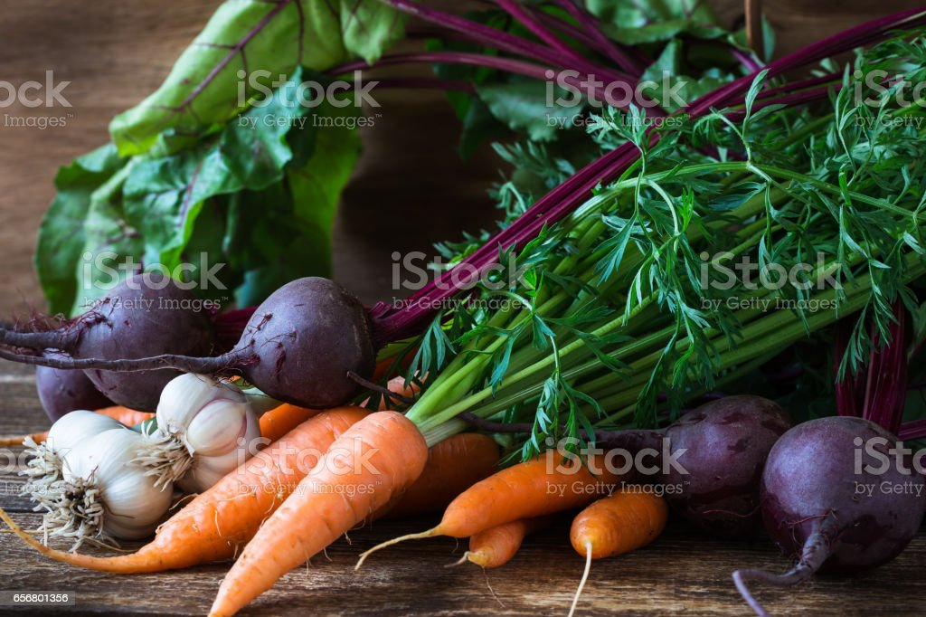 Bunch of fresh organic beetroots, garlic and carrots on wooden rustic table stock photo