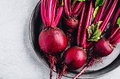 Bunch of fresh raw organic beets with leaves on a gray stone background