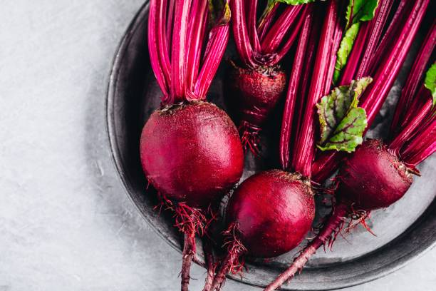 Bunch of fresh raw organic beets with leaves Bunch of fresh raw organic beets with leaves on a gray stone background beet stock pictures, royalty-free photos & images