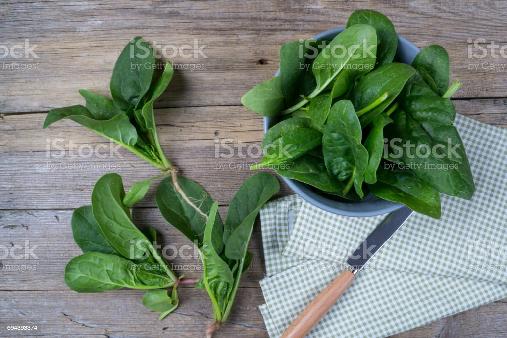 Bunch of fresh spinach with roots on rustic wooden background. stock photo