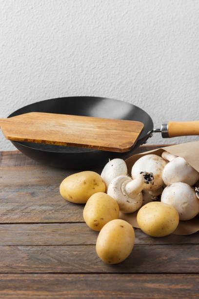 Bündel von frisch gepflückten weißen Knopf Pilze Kartoffeln in braunen Papiertüte Wok Skillet Schneidebrett auf rustikalen Holztisch – Foto