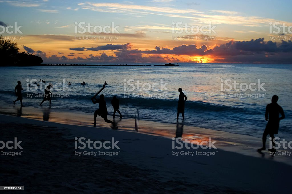 Bunch of friends playing cricket at the beach in Barbados stock photo