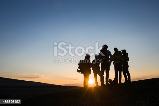 Friends hanging out at sunset in front a bright sun