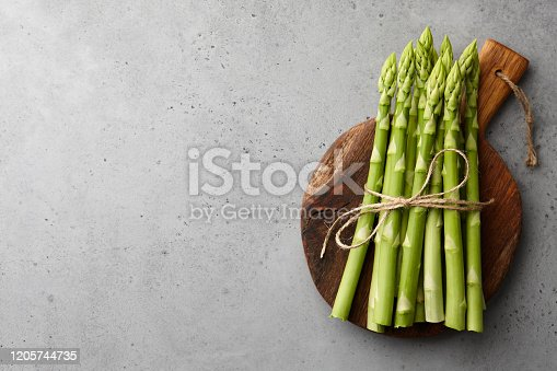 Bunch of fresh green asparagus on wooden cutting board on gray concrete background, top view