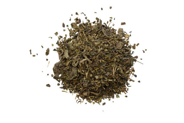 haufen von grünem tee auf weißem hintergrund - grüner tee koffein stock-fotos und bilder
