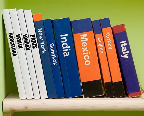 Bunch of guide books on a wooden shelf stock photo
