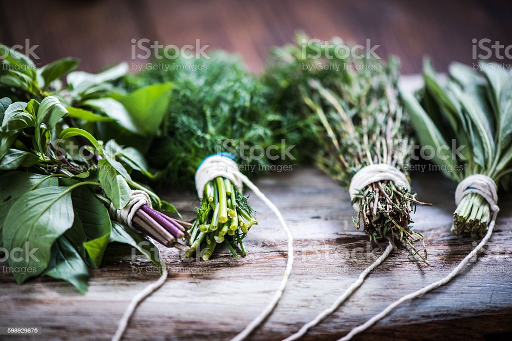 Bunch of herbs on wooden rustic board