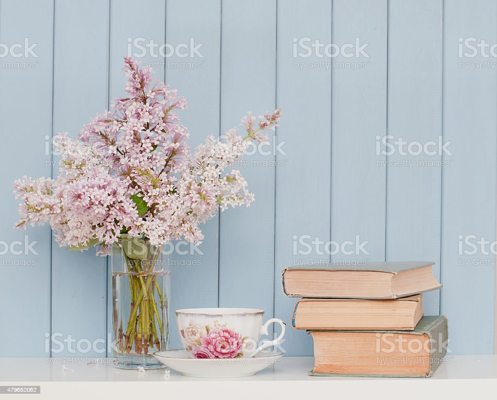 Bunch of lilac, books and teacup stock photo