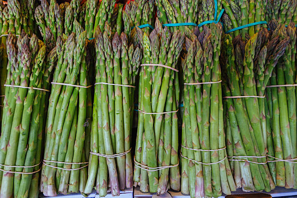 Bunch of mature asparagus standing on a greengrocer's shelf stock photo
