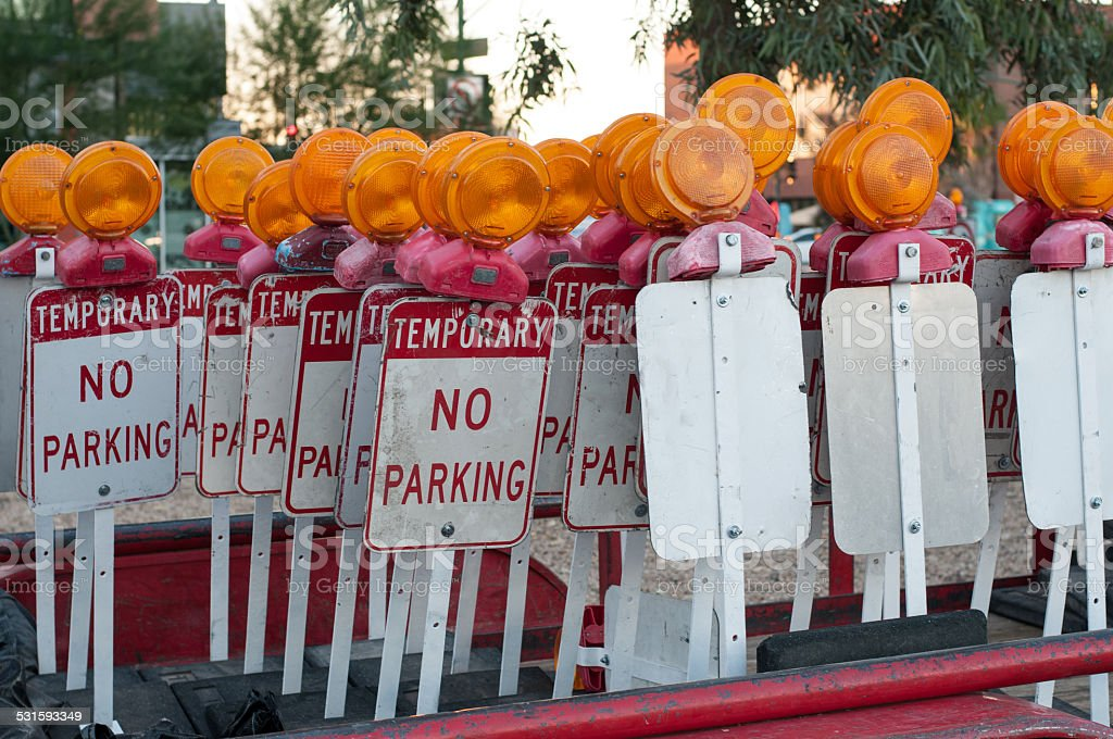 bunch of no parking signs ready to deploy stock photo