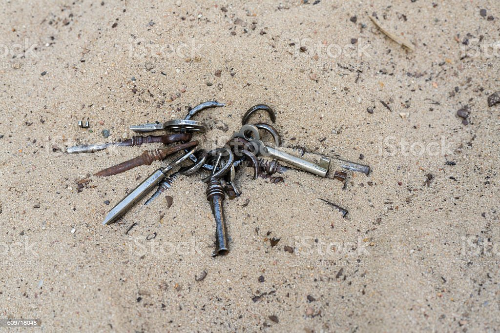bunch of old and rusty keys lost in the sand stock photo