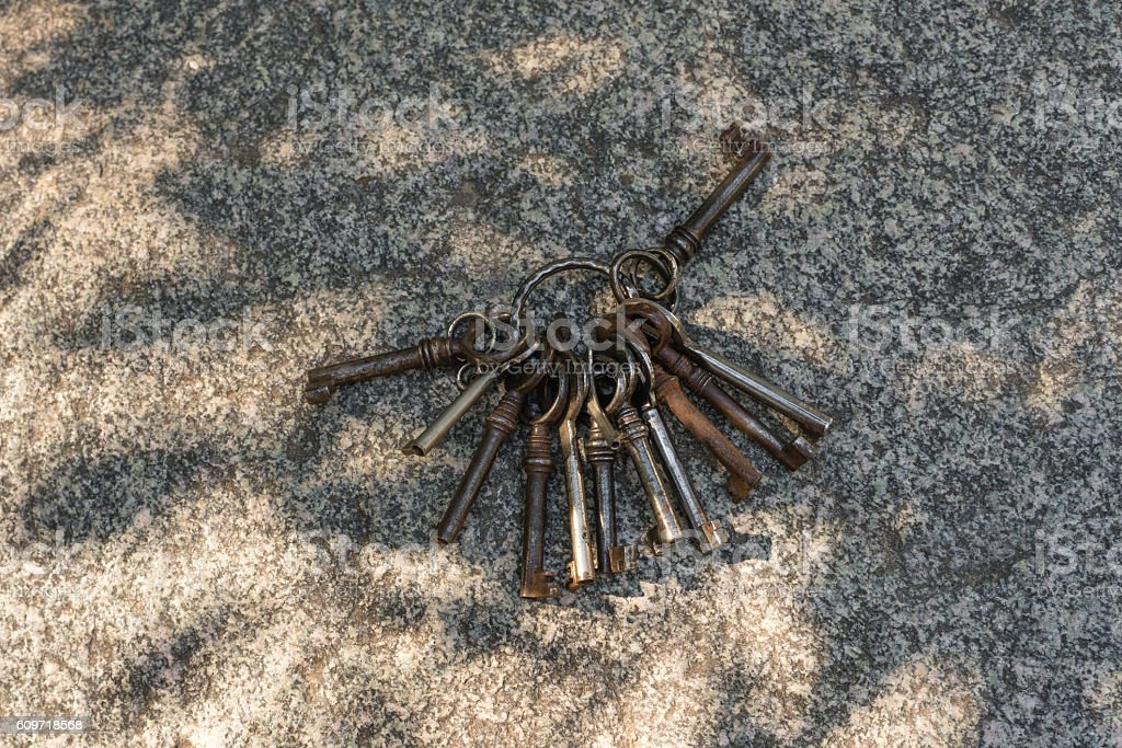 Bunch of old and rusty keys on a rock stock photo