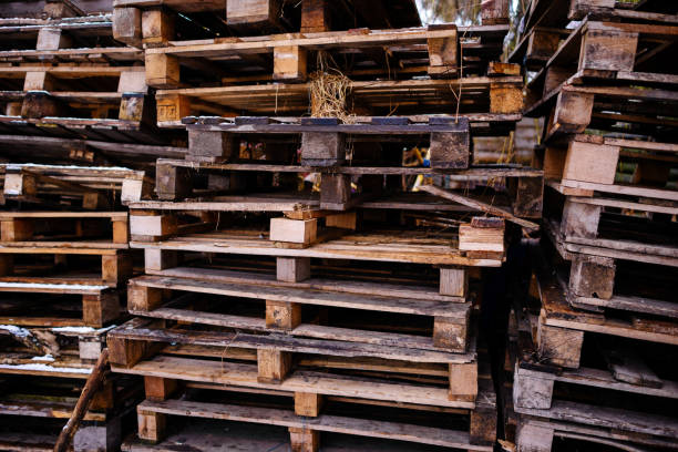 Bunch of old wet wooden pallets on green grass stock photo