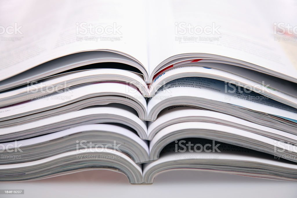 A bunch of open magazines stacked on top one another royalty-free stock photo
