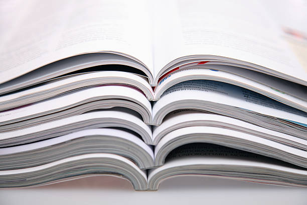 A bunch of open magazines stacked on top one another Magazines. See more:::: article stock pictures, royalty-free photos & images