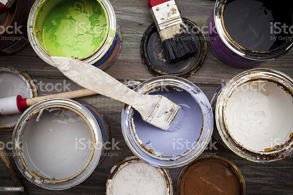 A bunch of open paint cans with brushes stock photo