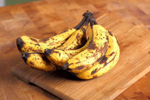 bunch of overripe bananas on a wooden background - ripe stock photos and pictures