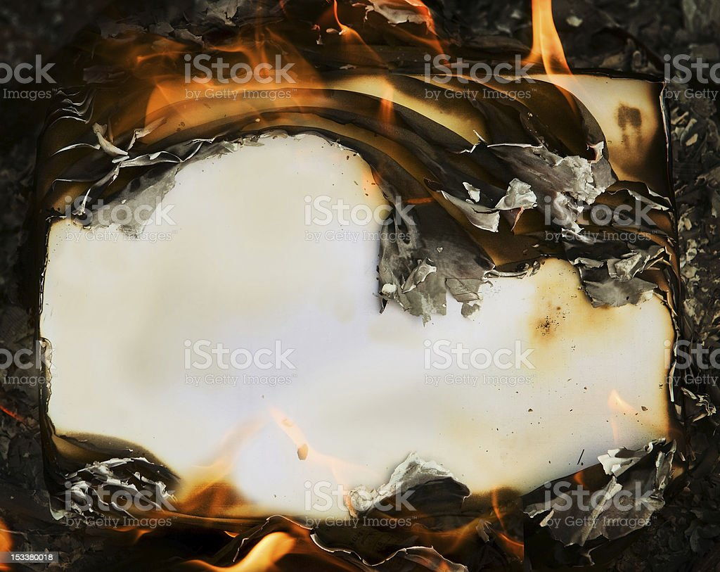 A bunch of paper burning on the ground stock photo
