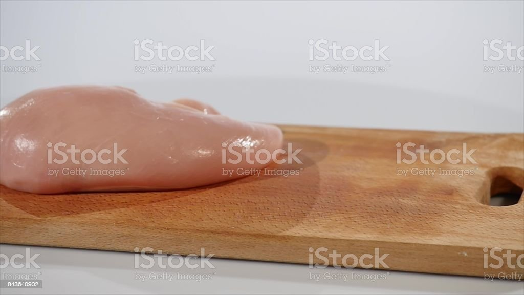 Bunch of parsley falls on chopping board near chicken fillet stock photo