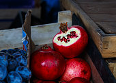 Blue plums and red pomegranates in wooden boxes at the market place