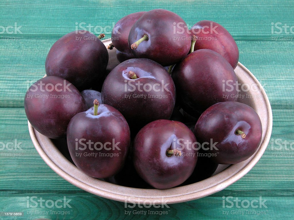 Bunch of plums in a bowl on a green table stock photo
