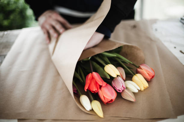 Bunch of rainbow tulips in brown paper wrap stock photo
