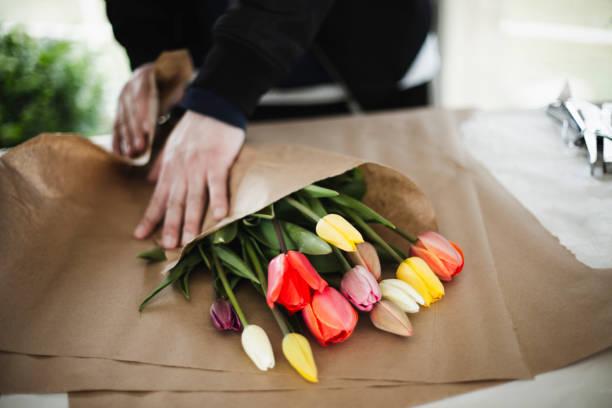 bouquet de tulipes arc en ciel en papier brun wrap - fleuriste photos et images de collection
