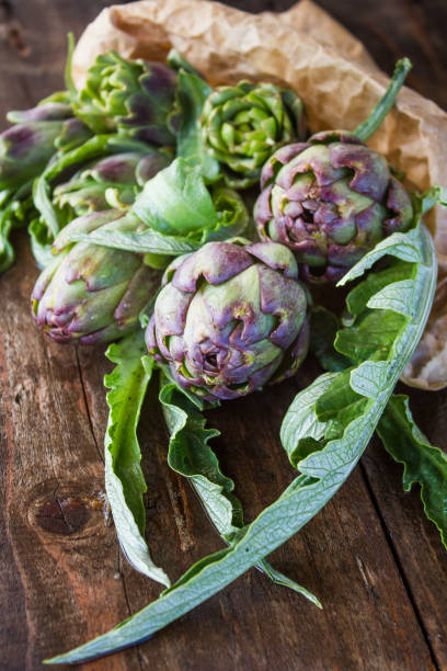 Bunch of raw artichokes in a paper bag on a wooden table. stock photo