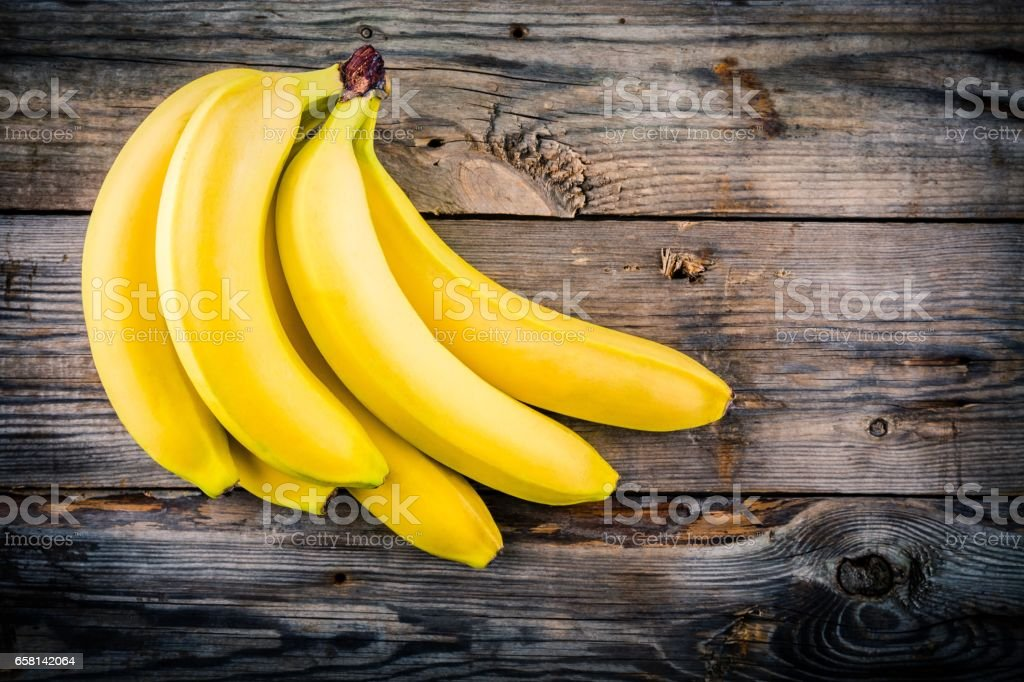 Bunch of raw organic banana on wooden background stock photo