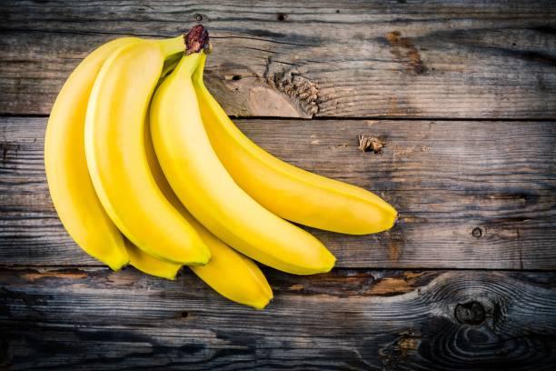 Bunch of raw organic banana on wooden background stock photo