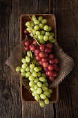 Fresh bunch of red and white grapes in a wooden on a dark wooden background